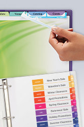 An open binder with a hand pulling the Easy Apply strips on Index Maker dividers to apply divider section titles